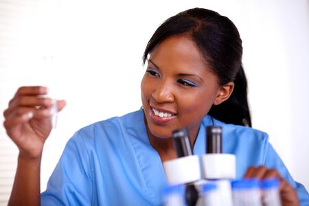 Scientific young woman looking to test tube at laboratory photo