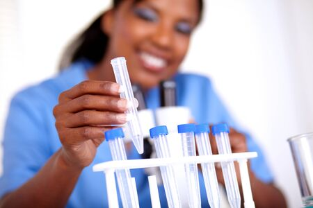 Scientific young woman working with test tube at laboratory photo