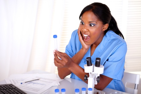 Surprised scientific woman looking to test tube at laboratory photo