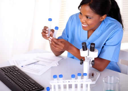 Satisfied scientific woman looking to test tube at laboratory photo