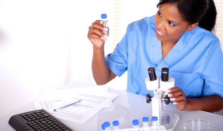 Beautiful scientific woman looking to test tube at laboratory photo