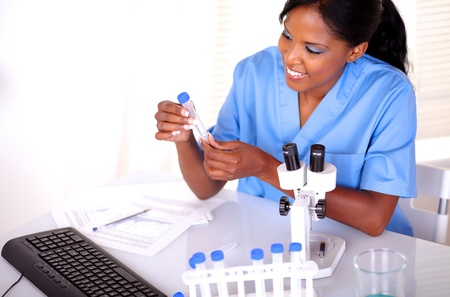 Beautiful scientific female looking to test tube at laboratory in blue uniform photo