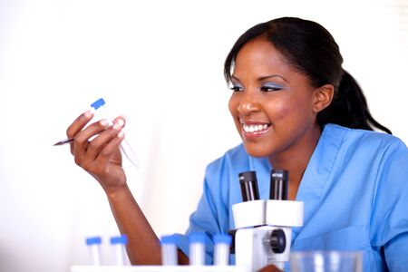 Smiling scientific woman working at laboratory in blue uniform photo