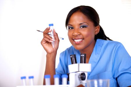 Scientific woman looking at you holding a test tube in blue uniform photo