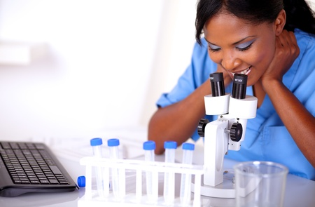 Scientific female in blue uniform working at laboratory with a microscope photo