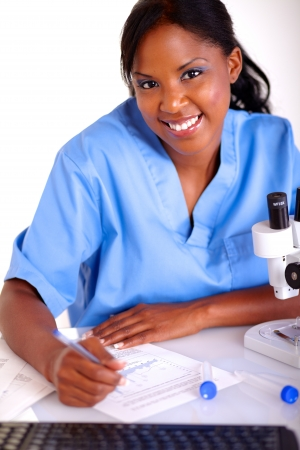 Scientific young woman looking at you while working with documents at laboratory photo