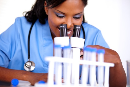 Medical doctor female working with a microscope at laboratory in blue uniform photo