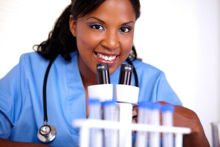 Medical doctor woman looking at you in blue uniform with a stethoscope at laboratory photo
