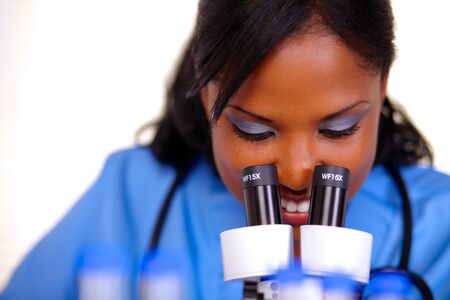 Charming medical nurse female using a microscope at laboratory in blue uniform photo