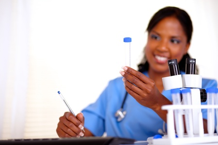 Afro-american nurse looking to test tube at laboratory - copyspace photo