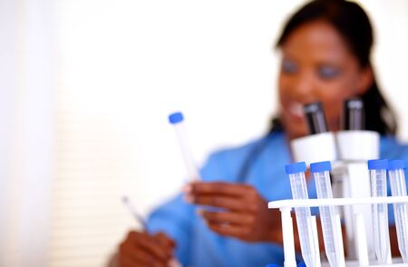 Afro-american nurse working with test tube at laboratory - copyspace photo