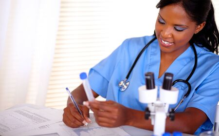 Afro-american nurse with a stethoscope in blue uniform working at laboratory - copyspace photo