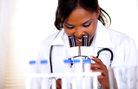 Medical doctor woman working with a microscope at laboratory photo
