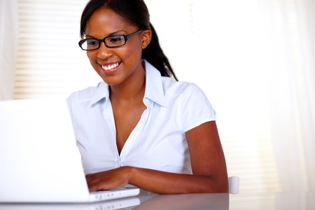 Smiling woman with black glasses working on laptop at office - copyspace Stock Photo - 15154850