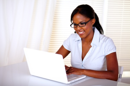 Charming woman browsing the internet on laptop at workplace with black glasses
