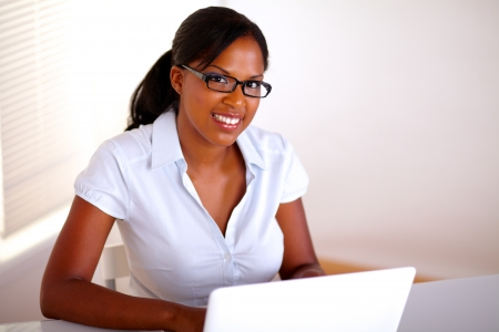Afro-american businesswoman looking at you in front of her laptop - copyspace Stock Photo - 15154873