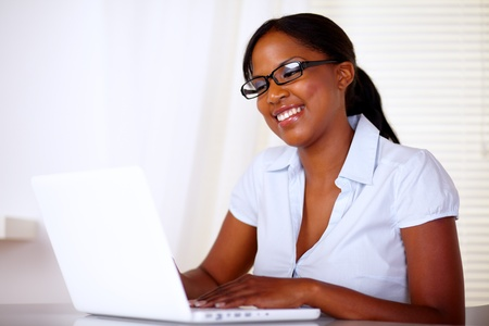 Lovely young woman smiling and looking to laptop screen photo