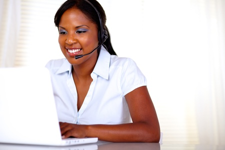 Attractive young call center operator working on laptop and speaking on microphone - copyspace photo
