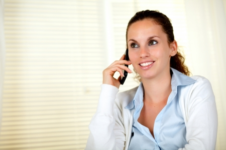 conversing: Charming caucasian female conversing on cellphone - copyspace