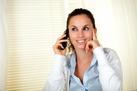 Charming young woman smiling while listening on cellphone at office - copyspace photo