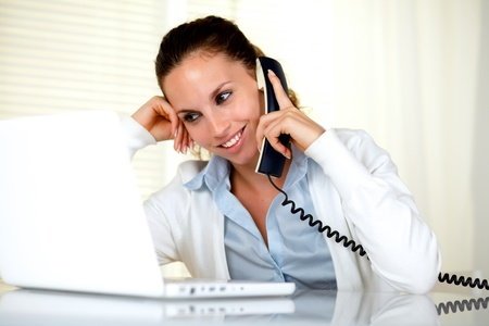 Smiling female conversing on phone while is working in front of laptop at office photo