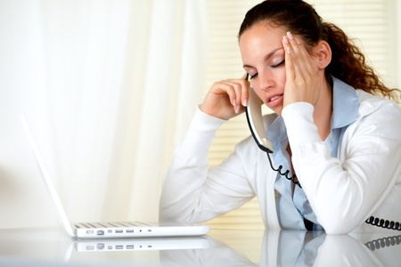 tired worker: Tired woman with headache speaking on phone in front of laptop at workplace Stock Photo