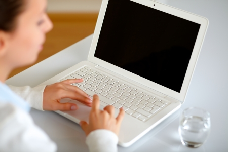 browse: Pretty young woman browsing the internet on her laptop at home