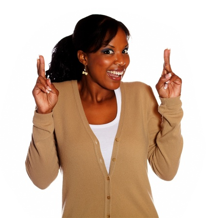 crossing fingers: Happy young woman with winning attitude crossing fingers and looking at you on isolated background