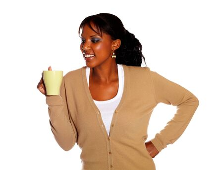 Smiling young woman looking to her mug against white background photo