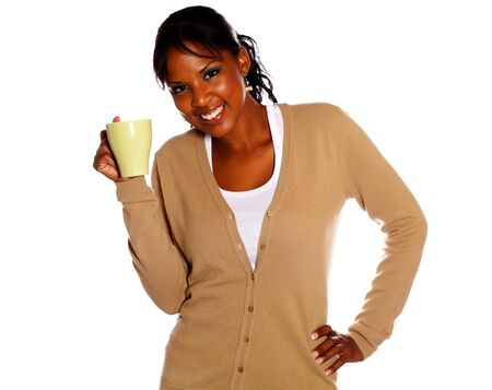 Afro-american young woman holding a mug and looking at you on isolated background photo