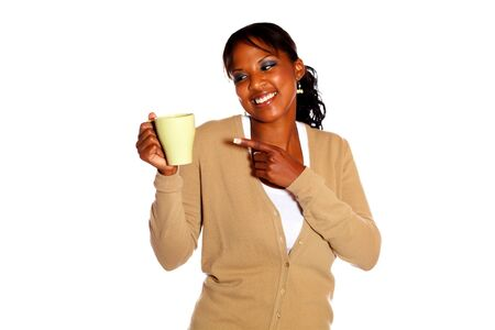 Smiling young woman looking and pointing a mug against white background photo