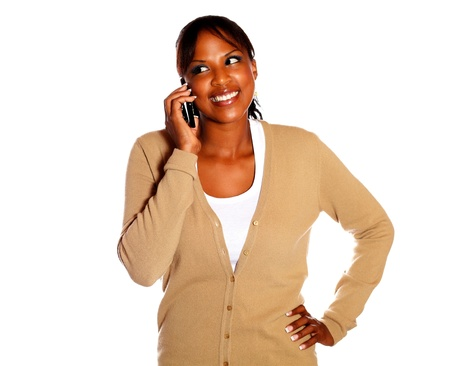 Charming young woman talking on cellphone against white background photo