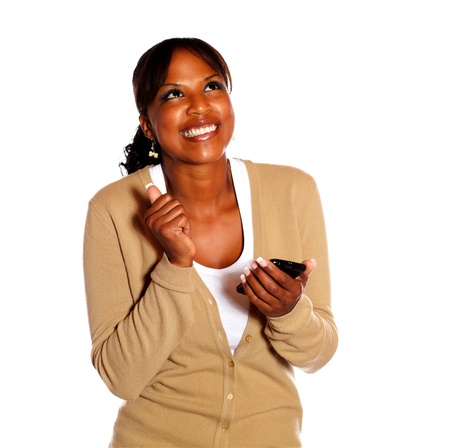 Happy young woman looking up with cellphone on isolated background