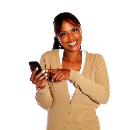 send sms: Smiling young woman looking at you and sending a message by cellphone against white background Stock Photo