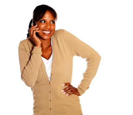Adult woman with a happy attitude speaking on cellphone against white background photo