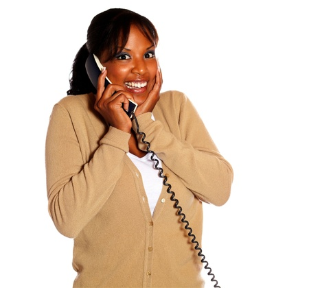 conversing: Happy young woman smiling and conversing on phone while looking at you against white background