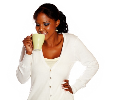 Attractive smiling young female drinking tea mug against white background photo