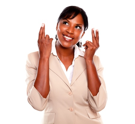 Young businesswoman looking up while crossing fingers against white background Stock Photo - 15599770