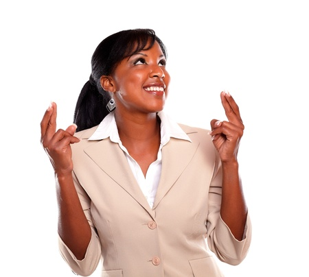 Young businesswoman looking left while crossing fingers against white background Stock Photo - 15599776