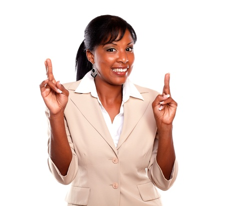Pretty businesswoman smiling and crossing fingers against white background Stock Photo - 15599710