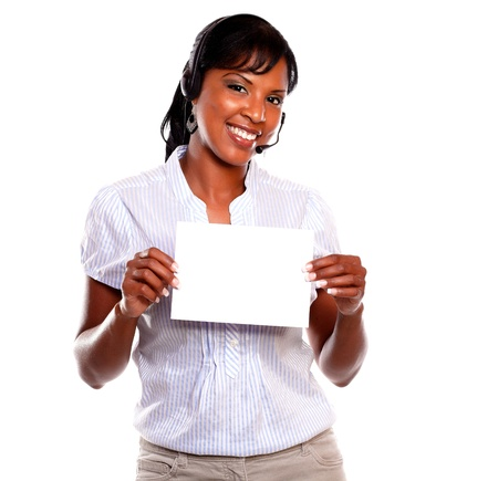 Adult female wearing headphones looking at you and holding white card on isolated background - copyspace