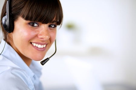 Hispanic young woman wearing headphone looking and smiling at you photo