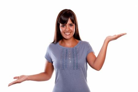 actitud positiva: Mujer joven sonriente que le mira con las manos en alto contra el fondo blanco - copyspace