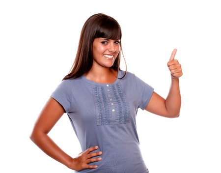 Charming young woman saying great job on blue shirt while is looking at you on isolated background photo
