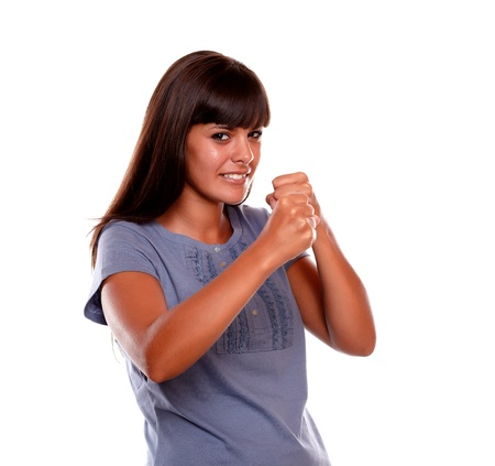 Angry latin young woman with clenched fists looking at you on isolated background photo
