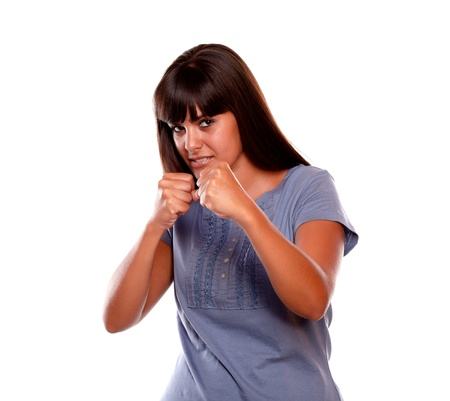 Angry latin young female with clenched fists looking at you on isolated background photo