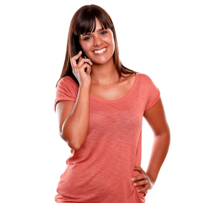 Beautiful young female speaking on cellphone while is looking at you against white background photo