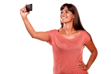 Smiling young woman taking a picture with her mobile phone on isolated background Stock Photo - 16254200