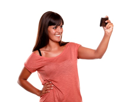 Smiling woman taking a picture with her mobile phone on isolated background photo
