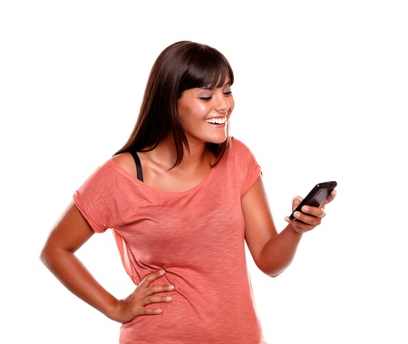 Young woman laughing while reading a message on her mobile phone against white background Stock Photo